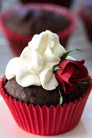 A Chocolate Cupcake With Red Casing Whipped Cream Icing And Small Rose