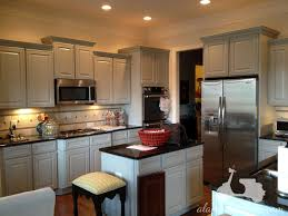 Kitchen White Wooden Cabinet And Island With Black Countertop Stool