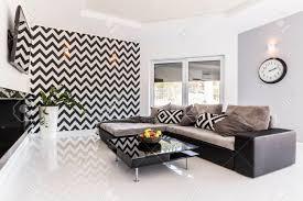 nobles wohnzimmer in schwarz und weiß mit großem ecksofa und gestreifter wand