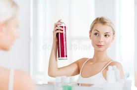 frau mit dem haarspray das ihr haar am badezimmer anredet