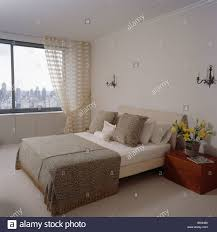 beige wurf und creme bettwäsche auf bett im schlafzimmer