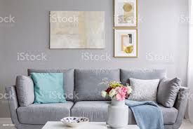 moderne malerei und zwei gold plakate hängen an der wand innen grau wohnzimmer mit sofa mit kissen und bunte blumen in keramikvase stockfoto und mehr