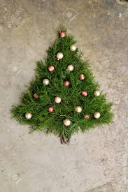 Christmas Tree Made Out Of Cedar Branches With Peach And Pink Ball Ornaments On It