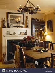 Wrought Iron Chandelier Suspended Above Wooden Table And Chairs In Front Of Fireplace