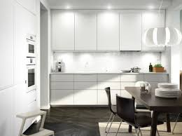 a white kitchen with white appliances and black brown leather