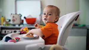 Booster Seat For Toddlers When Eating by Little Boy Child Practiced Eating At Home A Boy Sitting On The