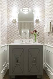 Lovely powder room features top half of walls clad in gray print wallpaper and bottom half