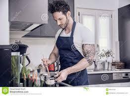 hübscher muskulöser mann in der küche kochend stockfoto