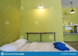 weißes minimales bett im schlafzimmer mit grüner wand