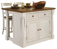 antiqued white kitchen island with granite top and two stools