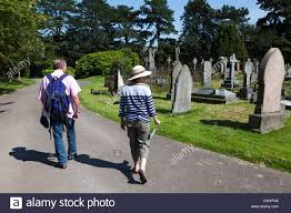 Two People Walking Through Cemetery Wales UK