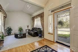 gemütliche sitzecke mit eleganten fenstervorhängen und gewölbedecke schwarz möbel set und viele töpfe mit grünpflanzen um das zimmer mit eingang