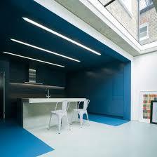 bureau change extension by bureau de change has blue kitchen and white lounge