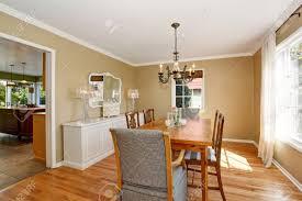 design interieur helles esszimmer mit holztisch weißem schrank mit spiegel und antikem kronleuchter