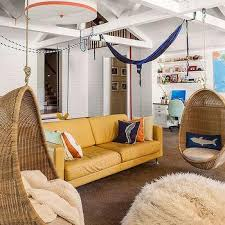 Beachside Living Room With White Truss Ceiling And Hanging Rattan Pod Chairs