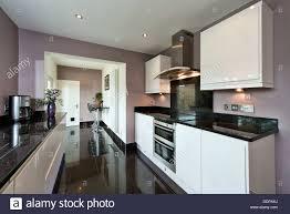 an installed clean modern designer kitchen in gloss white with