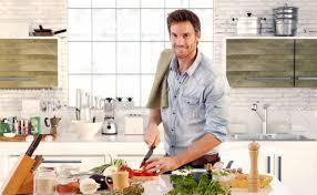 happy stattlicher mann in der küche kochen zu hause