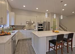 Contemporary Kitchen With White Cabinetry Wood Flooring And Aluminum Mini Pendant Lights