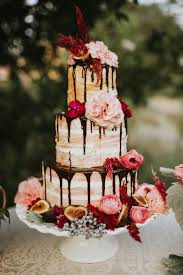 flower topped wedding cake with chocolate drizzle