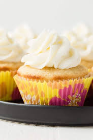 Pineapple Cupcakes With Coconut Buttercream Frosting On A Black Plate