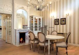 An Oval Shape Dining Table With A Classy Chandelier And Wooden Flooring