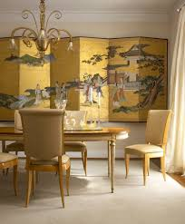 Chinese Decorative Screen In Gold Creates A Dramatic Backdrop For The Dining Room