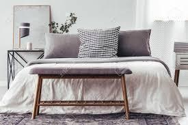 nahaufnahme der holzbank auf teppich gegen weißes bett mit gemusterten kissen im schlafzimmerinnenraum mit le auf tabelle