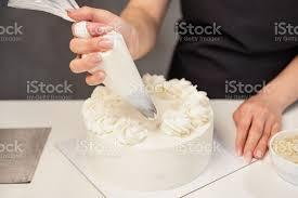 konditor bei der arbeit creme kuchen dekorieren kochtisch der einen kuchen zubereitet stockfoto und mehr bilder auszubildender