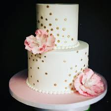 This Two Tier White Fondant Birthday Cake Features Gold Polka Dots In A Burst Pattern With Pink Ruffle Flowers