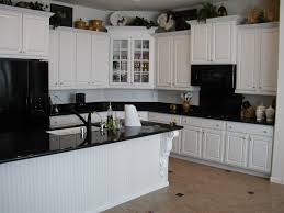 white kitchen cabinets with black appliances tile