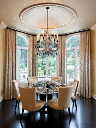 Gold Dining Room With Pedestal Table And Ebonized Hardwood Floor