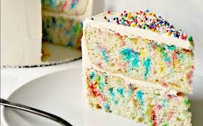 Slice of vanilla confetti birthday cake with sprinkles