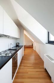 galley kitchen with skylights and white cabinets best lighting