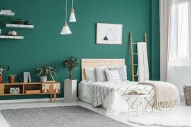 bed between ladder and plant in green boho bedroom interior with grey