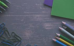 Colored Pencils On A Gray Desk With Paper Clips And Folders