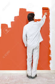 Man Painting A Wall With Orange Paint And Roller Stock Photo