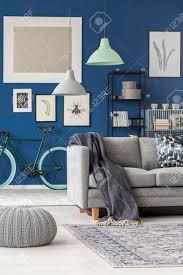 blaue decke die auf einer grauen in einem wohnzimmer mit grünem fahrrad gegen blaue wand liegt