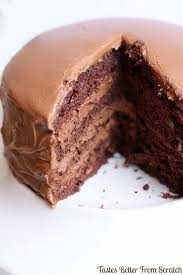 A large chocolate mousse cake on a white plate with a large slice cut out and