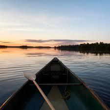 Decorative Oars And Paddles Canada by A Boat And Paddle On A Tranquil Lake At Sunset Lake Of The Woods