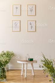 poster auf weiße wand im wohnzimmer interieur mit blumen und holztisch echtes foto stockfoto und mehr bilder blume