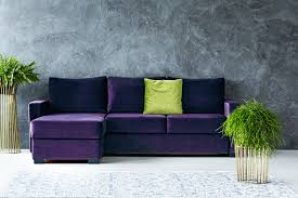 green cushion on purple corner against grey wall in living room