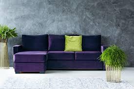 green cushion on purple corner against grey wall in living room