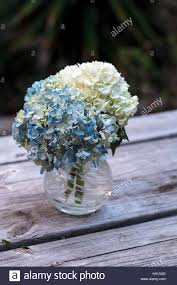 White And Blue Hydrangea Flowers In A Glass Vase On Rustic Wood Farm Table
