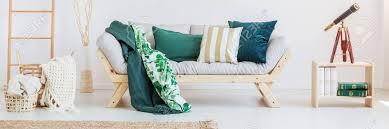 teleskop auf tabelle im wohnzimmer mit leiter stricken decke im korb und grüne kissen auf sofa