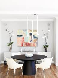 In This Modern Dining Room Colorful Abstract Art Takes Center Stage A Small Black Round Table Anchors The While Four White Molded Plastic Chairs