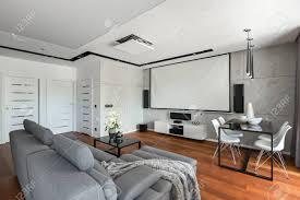 wohnzimmer mit sofa esstisch weißen stühlen und leinwand