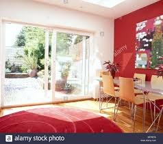 Dining Room With Red Accent Wall And Rug Table Chairs Open Sliding Glass Door To Garden