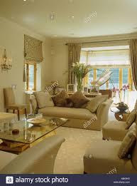 couchtisch aus glas und beige sofa und stühlen im wohnzimmer