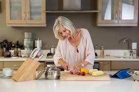 femmes plus cuisine femme plus âgée dans la cuisine coupant les légumes frais