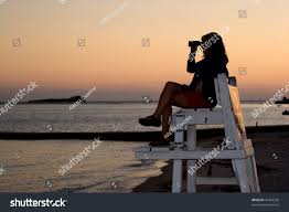 Beach Lifeguard Chair Plans by Silhouette Woman Looking Binoculars Beach While Stock Photo
